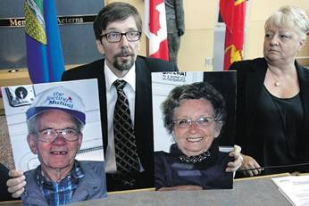 Bret McCann, above left, holds photographs of his missing parents, Lyle and Marie Ann McCann, during a news conference in July.